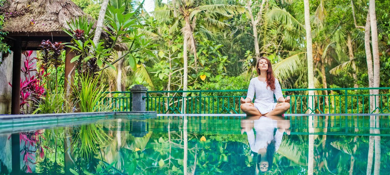 Blonde woman meditates in a beautiful tropical garden overlooking a reflective infinity pool