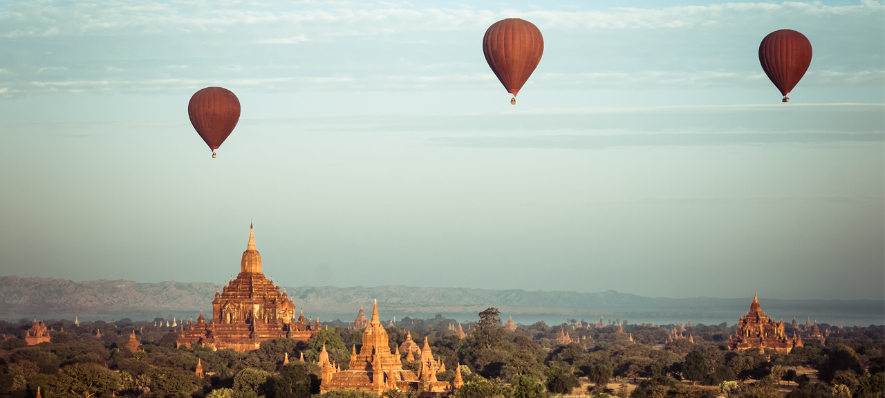 Hot air balloons flying at sunrise over ancient Buddhist Temples at Bagan, Myanmar (Burma)