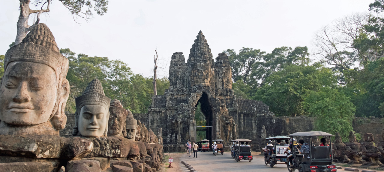 TukTuk drivers passing through the Gates of Angkor Thom in Siem Reap, Cambodia