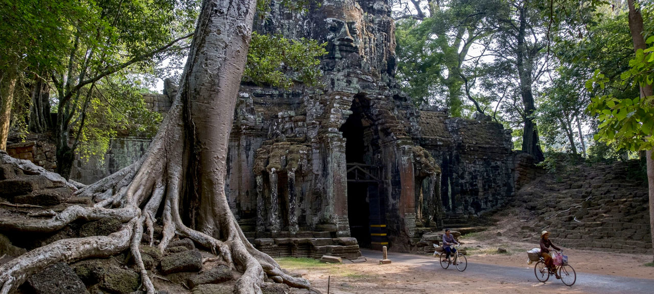 Couple Cycling Through The South Gates of Angkor Thom, Siem Reap, Cambodia