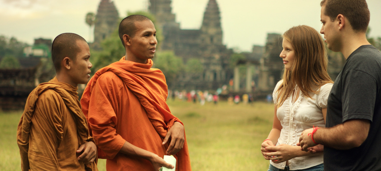 Couple speaking with a Buddhist Monk outside of Angkor Wat in Cambodia