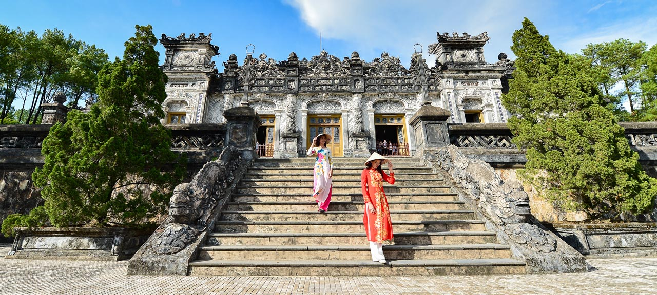 Women in traditional Vietnamese long dress walk down the steps of the imperial palace in Hue, Vietnam