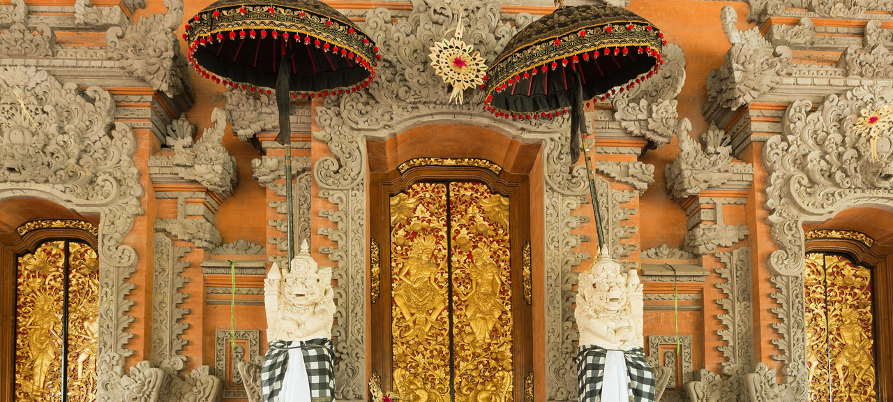 Gods holding umbrellas in frot of golden doors at a temple in Bali, Indonesia