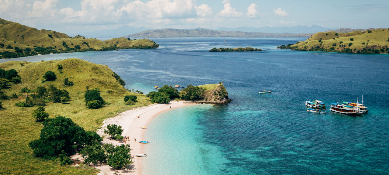 Sunny day view of a pink beach with turquoise sea and tourist boat on the Island of Flores, Indonesia