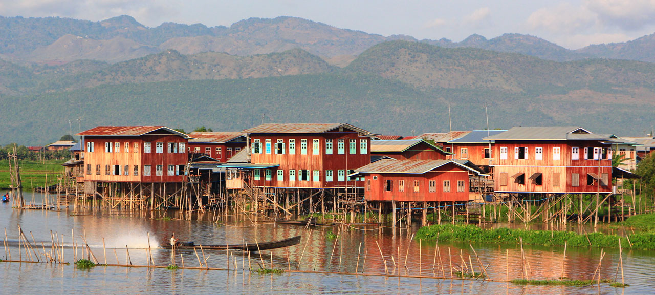 Boat Passes By The Floating Village in Inle Lake Myanmar at Sunrise