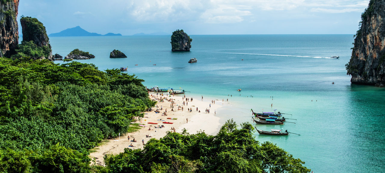 Swimmers enjoy the gorgeous white beaches and blue waters of the Andaman sea in Krabi Province, Thailand