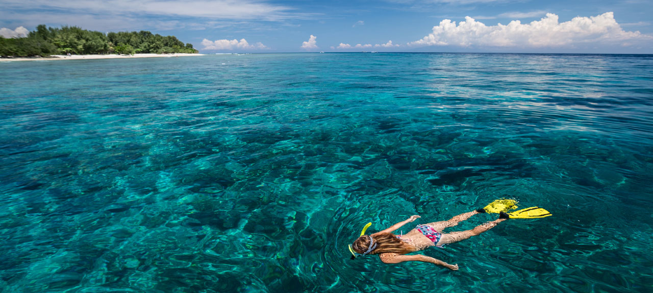 Woman snorkeling in turquoise water near Gili Trawangan island, Indonesia