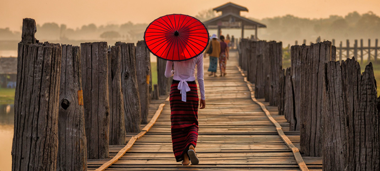 Burmese girl holding a red umbrella walking on U Bein Bridge in the morning in Mandalay Myanmar