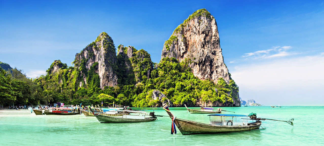 Limestone Mountains Behind Longtale boats floating in the sea at a beautiful beach in Phuket, Thailand