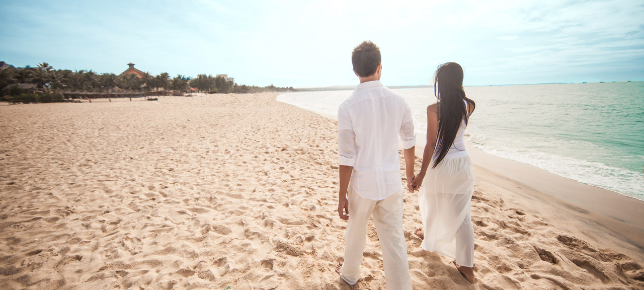 Honeymoon couple walking hand in hand down a beautiful white sand beach