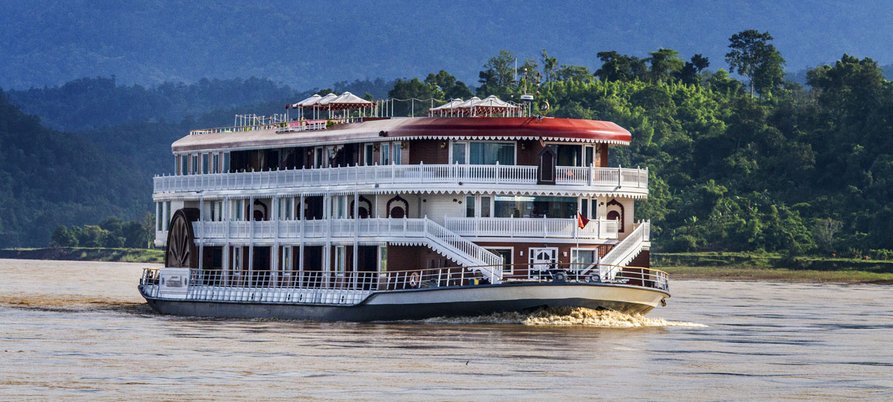 Antique styled luxury river cruise boast traveling at sunset along the Ayeyarwady River in Myanmar