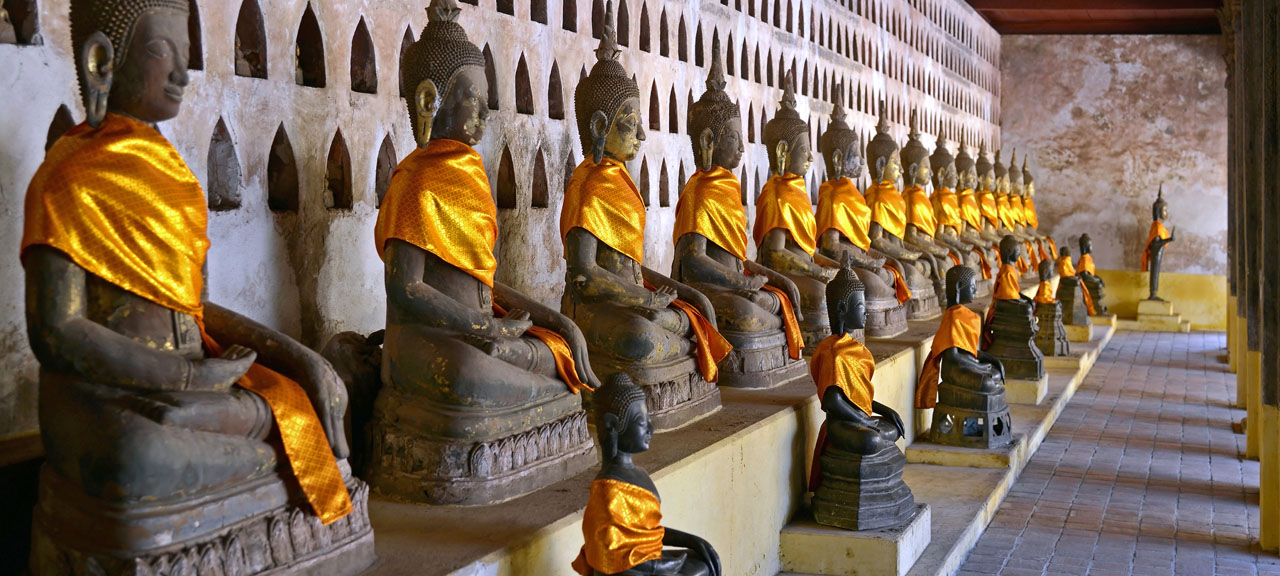 16th Century Buddhas in Wat Sisaket wearing gold silk in Vientiane city Laos