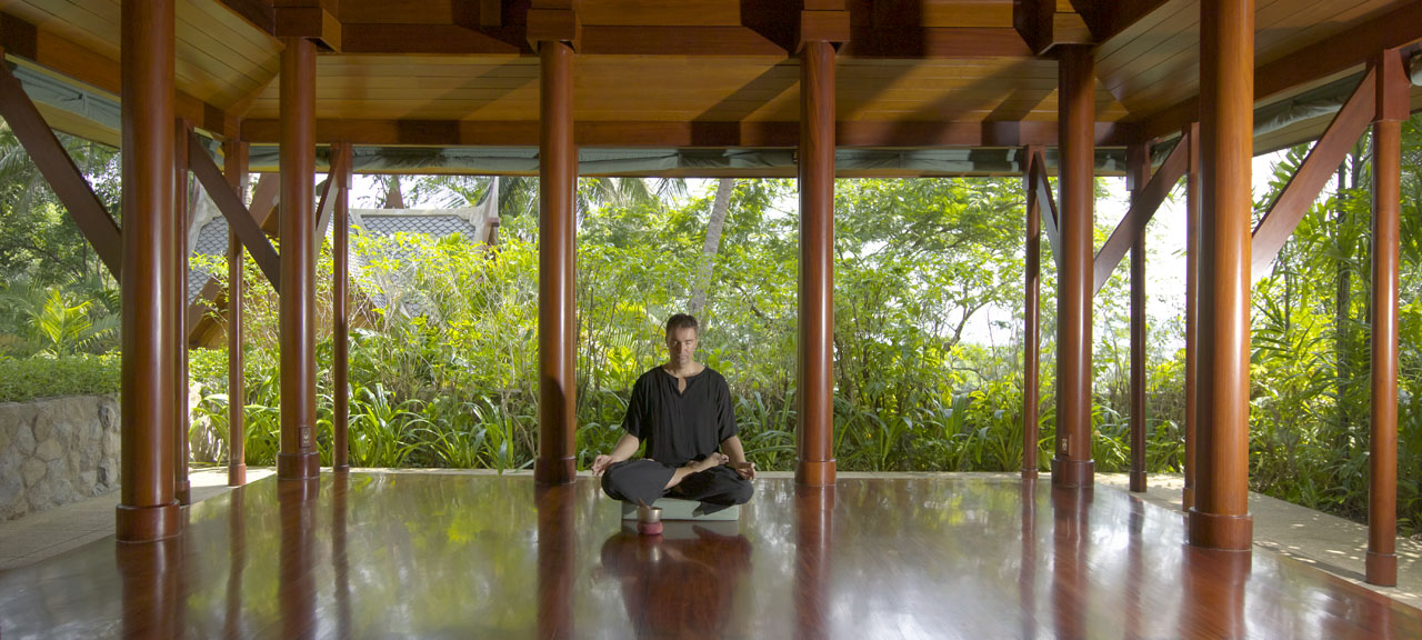 Man sits on a wooden atrium outside in a lush green jungle at the Amanpuri Wellness Retreat in Phuket, Thailand