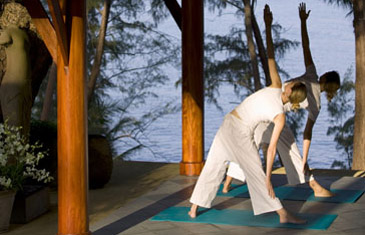 Woman in white practicing yoga outside at the Amanpuri resort