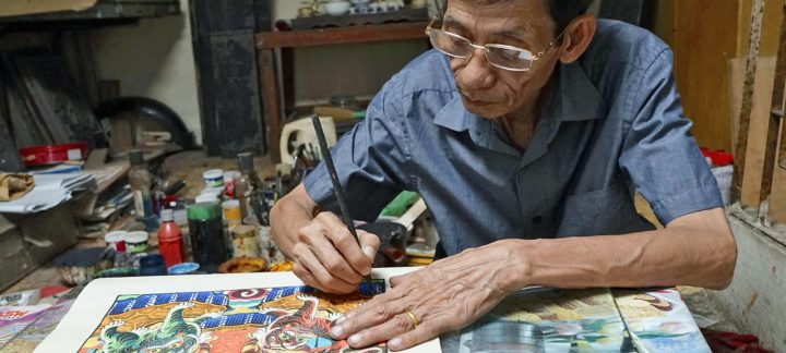 A traditional Vietnamese artist paints in his art studio, Hanoi, Vietnam