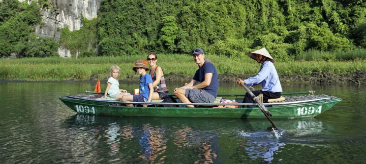Multi generational family traveling on a river in a green canoe in Vietnam