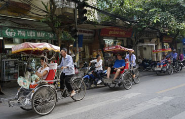 Families traveling along the busy Hanoi Streets in a rickshaws