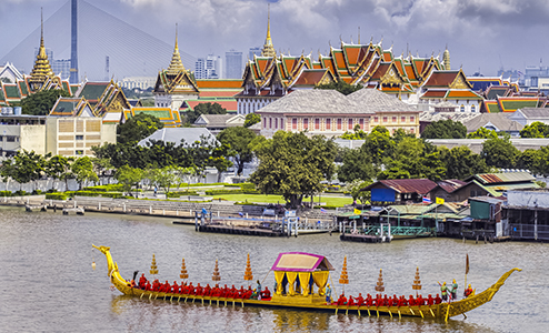 View of a pagoda across the river with a traditional Thai boat floating by on a sunny day in Bangkok