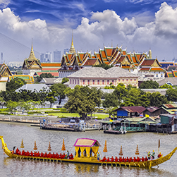 A pagoda across the river with a traditional Thai boat in the foreground on a sunny day in Bangkok