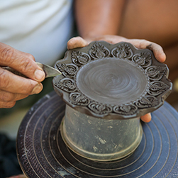 Close up view of a Thai artisanal potter decorates a traditional ceramic dish in Bangkok