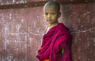 Novice Monk sits in front of old building