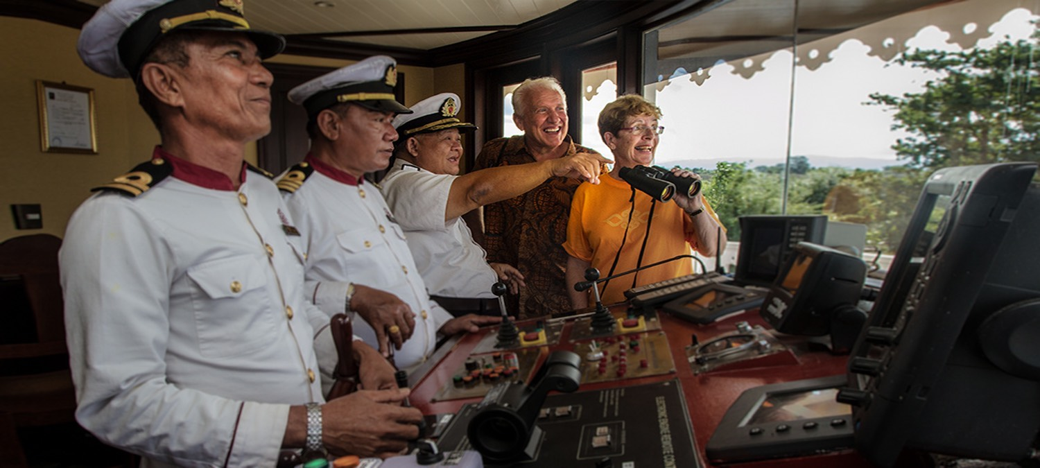 Guests at the ships helm aboard Heritage Line's The Jahan cruising along the Mekong River