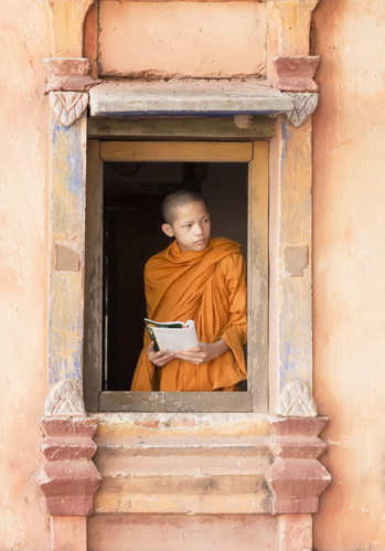 Young monk in a orange robe looks out a terra-cotta colored window in Cambodia