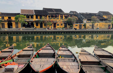 View of the yellow historic buildings in Hoi An Town looking over the river from a row of boats on one side