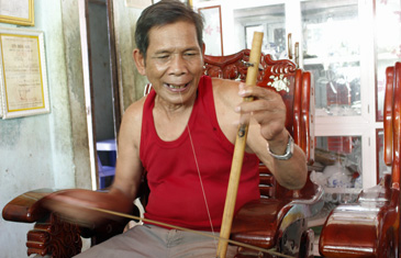 Man in a red shirt entertains guests with a performance of typical Co Tu musical instruments in Hoi An, Vietnam