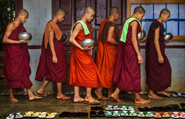 Young monks in red robes line up to receive alms for their morning breakfast in Myanmar