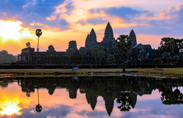 The Angkor Wat Complex in silhouette at sunset reflected in a man made pond in Cambodia