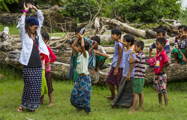 Local community dancing together in celebration on the riverbanks of the village of Yandabo