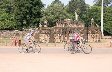 3 people cycle past ruined portions of the Angkor complex in Seim Reap, Cambodia