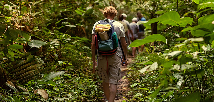 Man hikes wearing a yellow and green back pack on a tour through the Cambodian Jungle