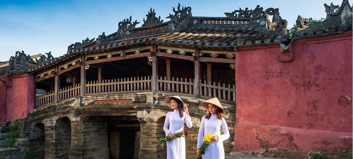 Two young women in traditional Vietnamese dress walk beside the Japanese Bridge in Hoi An, Vietnam