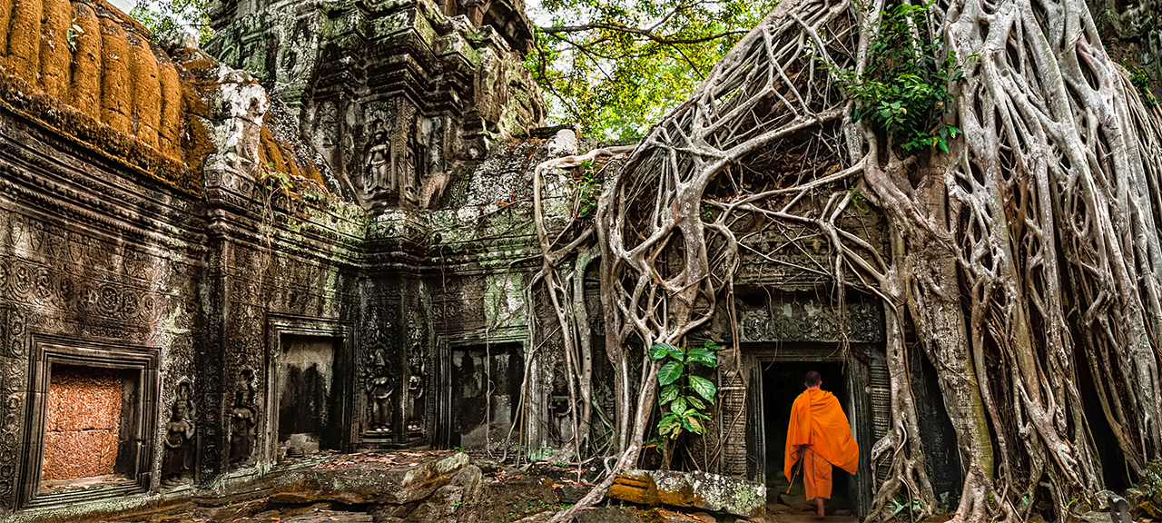 A Buddhist monk in an orange robe walks through the ancient temple door way at Ta Prohm, Seim Reap