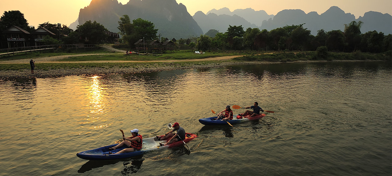 People kayaking down a river at sunset in northern Laos