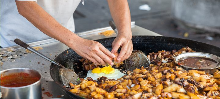 Man cracking an egg into a large wok, Malaysian street food