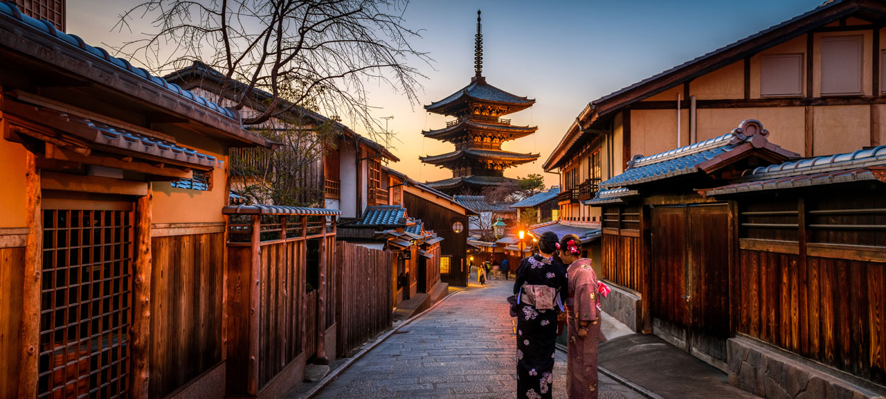 Two young girls dressed in Kimono walk towards a pagoda at sunset in Kyoto
