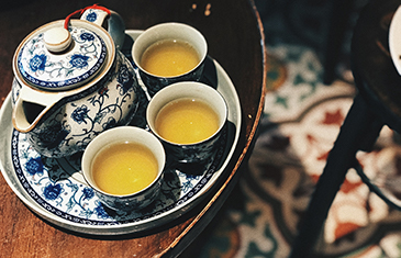 A beautiful setting of Chinese tea served in white and blue traditional ceramic tea cups from a matching tea pot