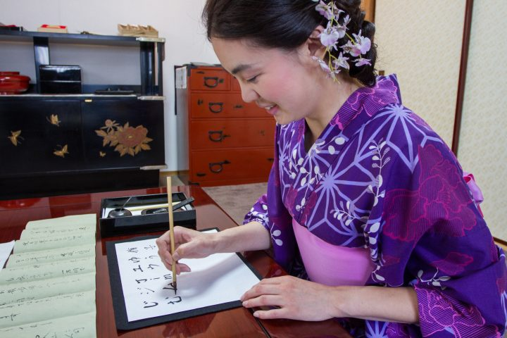 Young Japanese girl in Violet Kimono learning the ancient art of Japanese Calligraphy