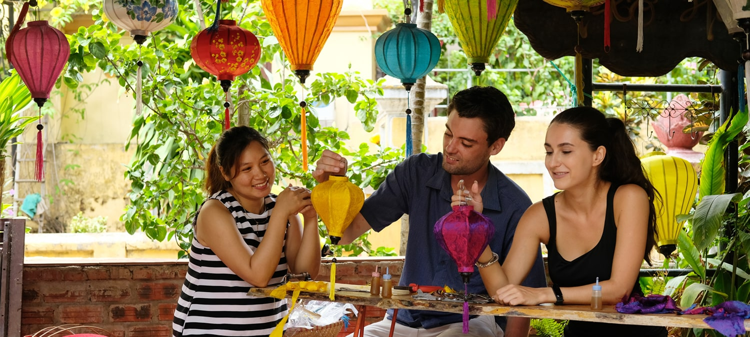 Young couple learns how to make Vietnamese traditional lanterns in hoi an