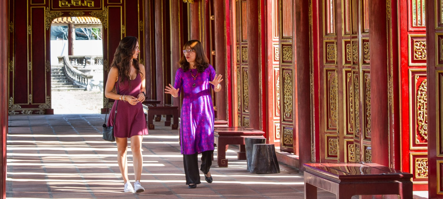 Young woman learns about the imperial Palace in Hue with a historian walking through its halls
